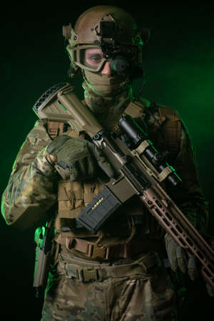a soldier in military clothing with a night vision device and on a dark background