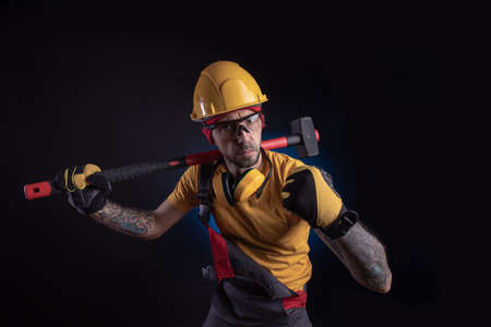 the male construction worker with a sledgehammer Foto de archivo