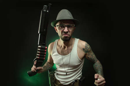 an athletic guy with a tattoo poses with a shotgun