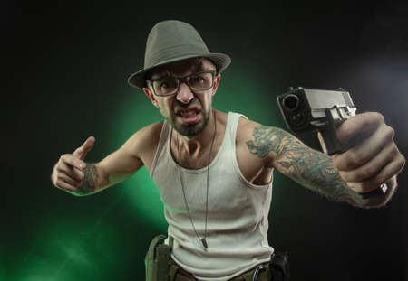 an athletic guy with a tattoo poses with a pistol