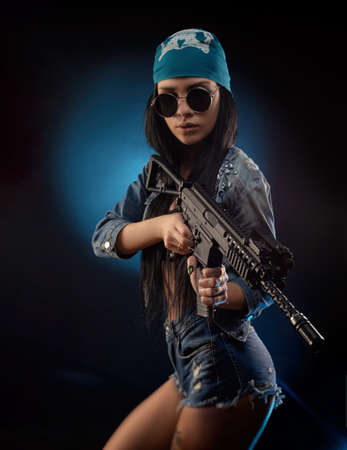 a girl in a DENIM jacket with an AUTOMATIC RIFLE