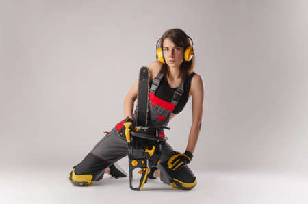 Girl in overalls with a chainsaw in white background Standard-Bild