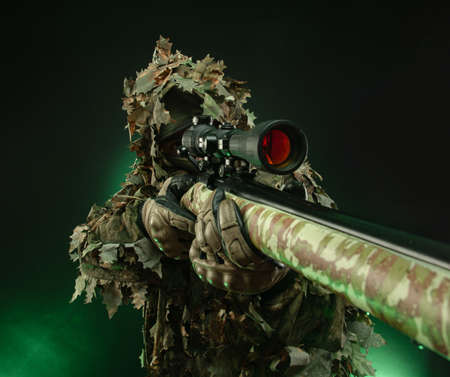 sniper in a poncho camouflage suit and a sniper rifle