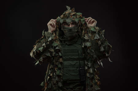 sniper in a camouflage suit poncho with a gun