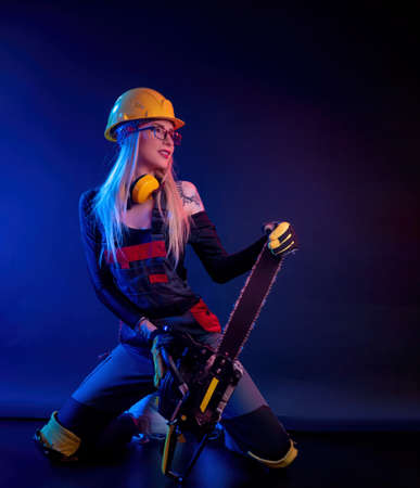 a girl with a chainsaw in overalls on a black background in a neon light