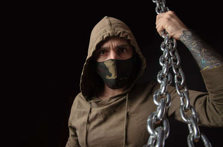 guy in a mask and hood with chains