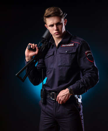 a guy in a police uniform with a short barreled automatic rifle with a telescopic sight takes aim. english translation Police