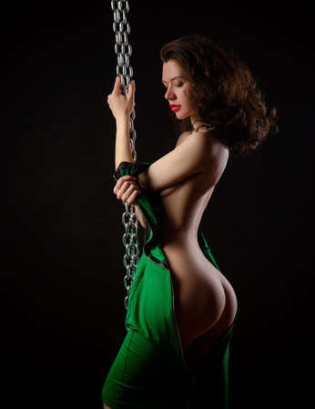 Nude sexy girl in green dress with chains