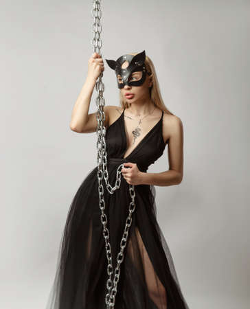 Beautiful blonde in a cat mask in a sexy evening dress on a white background posing with metal chains Archivio Fotografico