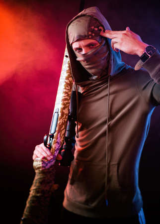 a guy in a Balaclava with a sniper rifle in the neon light Standard-Bild