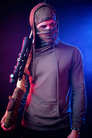 a guy in a Balaclava with a sniper rifle in the neon light