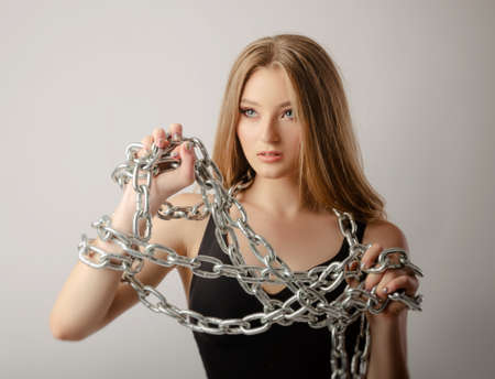 a girl in a bodysuit poses with a large chain in her hand.