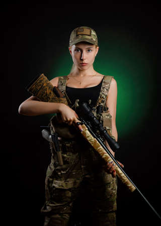 a girl in military airsoft overalls poses with sniper rifle on a dark background Standard-Bild