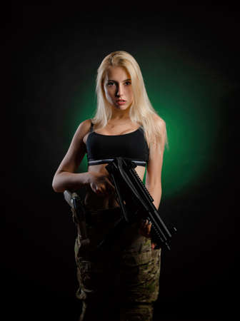a sexy girl in military airsoft overalls poses with a assault rifle on a dark background
