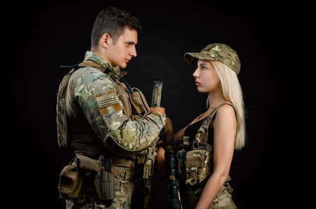a girl and a guy in military overalls pose with an airsoft gun on a dark background
