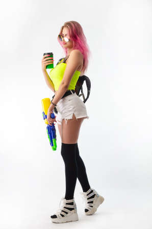 girl with a water gun in summer clothes, slim and sexy isolated on a white background