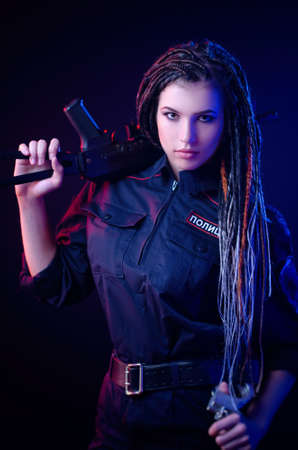 a girl in a police uniform with dreadlocks in neon light English translation of the police 스톡 콘텐츠