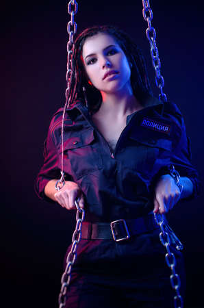 a girl in a police uniform with dreadlocks in neon light with chains and handcuffs English translation the police