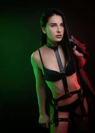 beautiful hot brunette girl posing in a photo Studio on a dark background d leather raincoat neon light