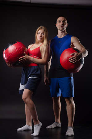 athletic man and girl stand with balls in their hands on a dark background