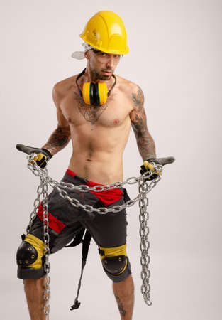 a man in a construction repairmans overalls holds a metal chain in his hands