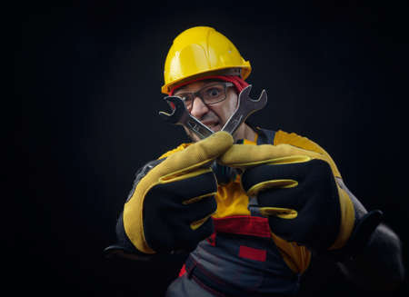 a guy in overalls and a construction helmet with a wrench