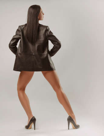 A brunette girl on  white  poses in a stylish leather jacket standing backwards with bare legs