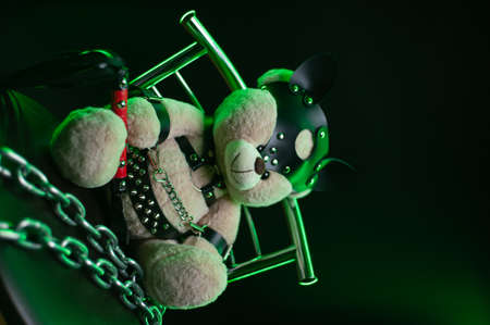 toy bear dressed in leather belts harness accessory for games on a dark background
