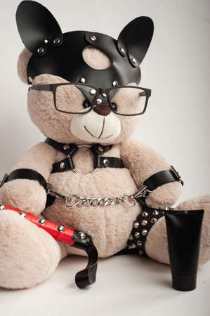 toy bear dressed in leather belts harness accessory for bdsm games on a light background Foto de archivo