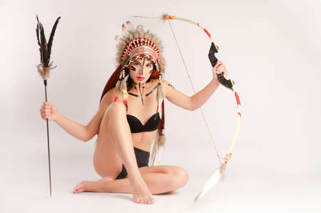 girl in the image of indigenous peoples of America with a bow and arrow posing on a light background