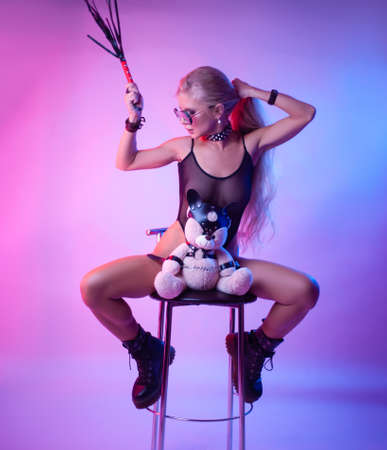 Sexy blonde with long hair sits on a chair with a toy bear in bdsm accessories Banco de Imagens