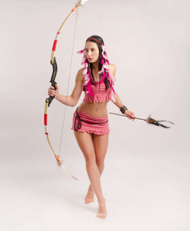 slender girl in an Amazon costume with a bow and arrow in her hands Stock fotó