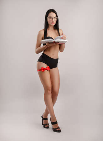 Slender brunette with glasses dressed in underwear with a red butterfly on her leg photo on a white background holding a book Stock fotó - 155433306