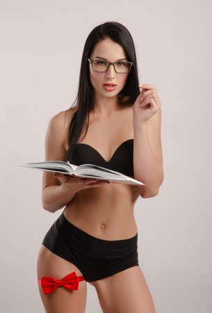 Slender brunette with glasses dressed in underwear with a red butterfly on her leg photo on a white background holding a book Stock fotó