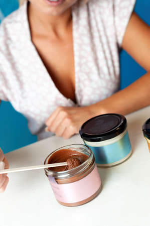Blonde woman sits at a table with vegan paste in jars Фото со стока
