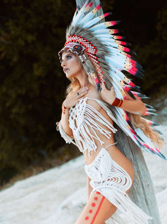 a woman in the image of the indigenous peoples of America posing in nature