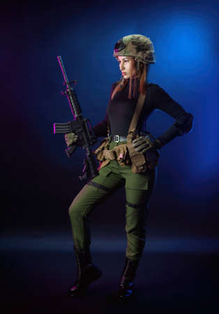 a woman in military airsoft uniform with an American automatic rifle and pistol on a dark background