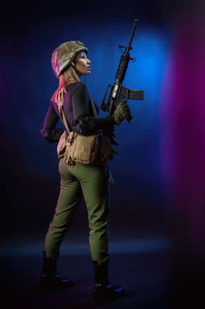 a woman in military airsoft uniform with an American automatic rifle and pistol on a dark background Stock Photo