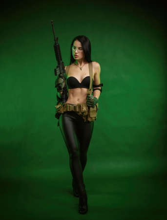 slender woman in military fatigues with an American automatic rifle on a green background