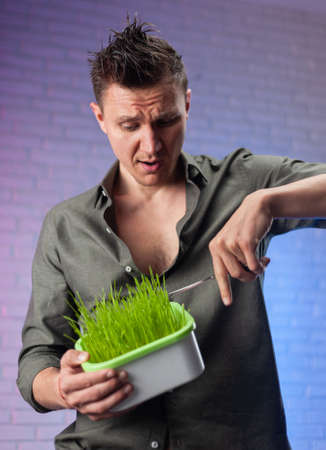 a man holds a seed germinator with growing green wheat and scissors
