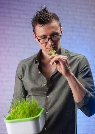 a man holds a seed germinator with growing green wheat