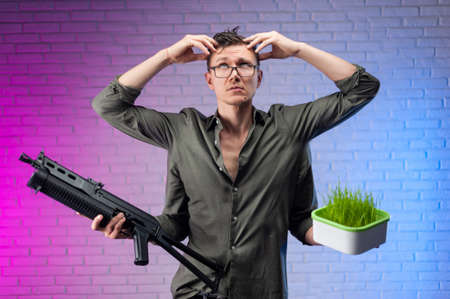 a man with four hands holds a sprouter of growing green wheat in one hand and an automatic rifle in the other and holds his head.
