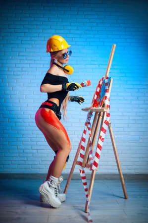sexy woman in a construction helmet in the image of plaster with a brush draws on an easel Imagens