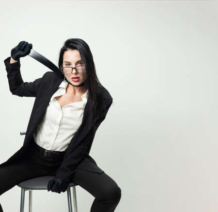 a woman in black office clothes and gloves is sitting on a chair with a belt around her neck