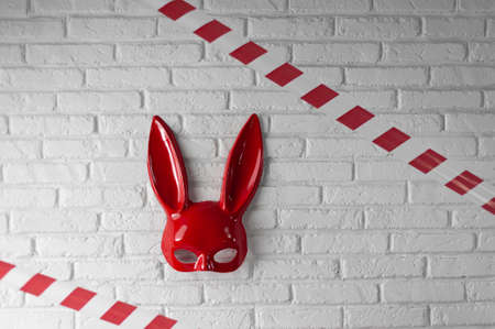 red rabbit mask on a white brick texture wall and red and white signal tape