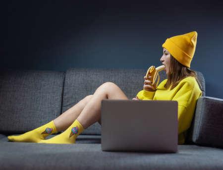 Woman on sofa with laptop eating banana