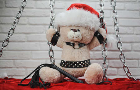toy Teddy bear dressed in leather belts and a Santa Claus hat in the new year chained and handcuffed accessory for BDSM games on a light background texture of a brick wall