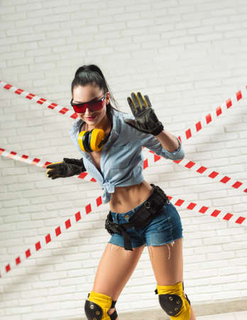 a slender woman in the image of a construction worker in gloves dances and has fun against the background of a white textured brick wall Standard-Bild