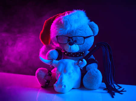 a toy bear in a Santa Claus hat wearing leather straps harness accessory for BDSM along with a statuette of a white bull on a dark background in neon light