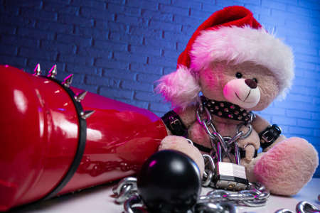 a toy bear in leather belts and a Santa Claus hat in the New year Christmas is chained and handcuffed an accessory for BDSM games next to a fire extinguisher Фото со стока